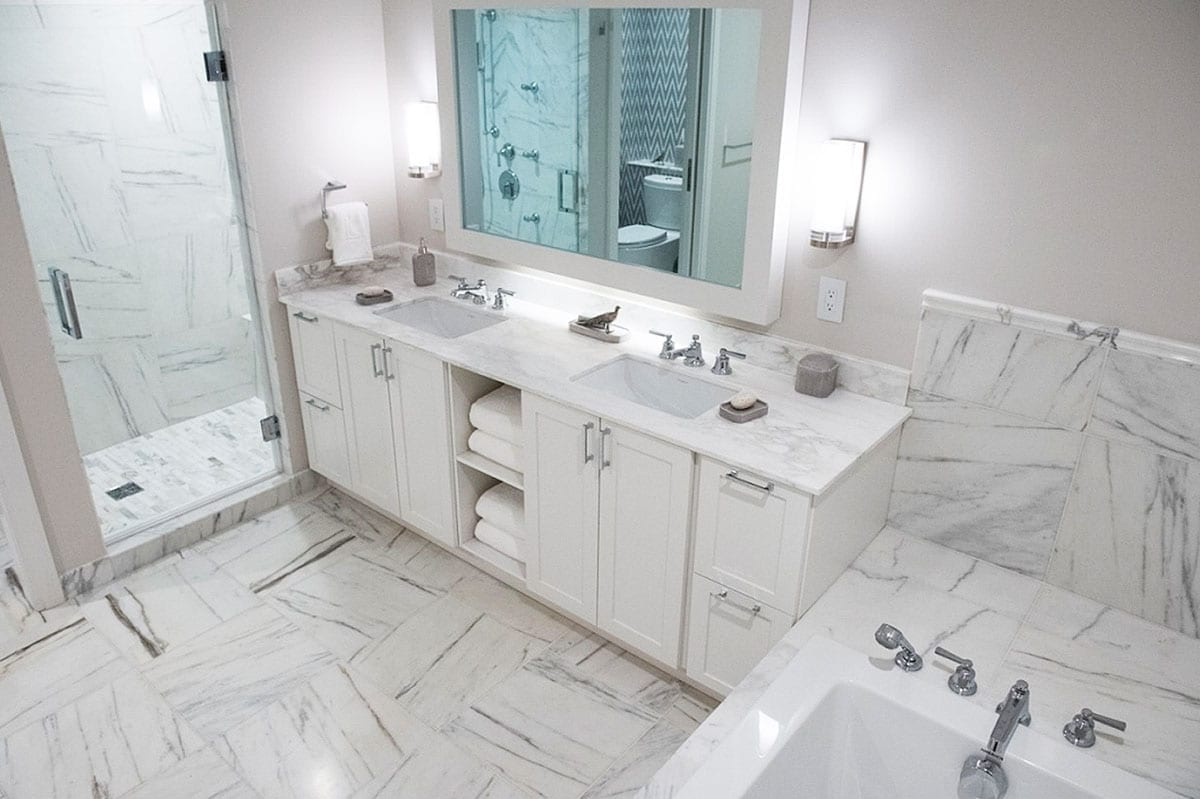 The master bathroom has a TV screen hidden in the mirror, a standard feature at the Lauren; marble flooring and double sinks. (Sarah L. Voisin/The Washington Post)